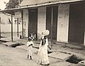 Collectie Nationaal Museum van Wereldculturen TM-60062125 Vrouw op straat met een bundel op haar hoofd, achter haar een meisje Trinidad en Tobago fotograaf niet bekend.jpg