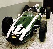 Photograph of the front of the Cooper T51 racing car. It is fairly cylindrical in shape, coloured green, with two white racing stripes, and the number 17 on the bonnet.