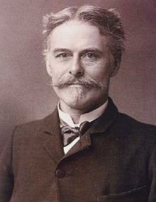 Head and shoulders of a middle-aged man who is looking at the viewer: He has a moustache and goatee, and his hair is short and parted in the middle. He is wearing a formal jacket, with a bow tie and wingless collar.