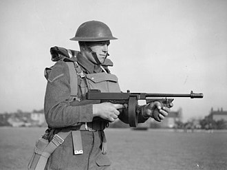 Marching fire - A British soldier demonstrates proper marching fire technique using a Thompson submachine gun with a 50-round drum magazine