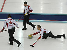 At The  Winter Olympics Mark Nichols From Team Canada Delivers A Stone While His Teammates Look On Ready To Begin Sweeping The Curler Uses His Broom