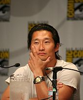 An Asian man wearing a white shirt sits in front of a microphone.