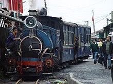 Trajno, transportita de vaporlokomotivo, kurante apud vojo inter du vicoj de konstruaĵoj kie kelkaj homoj piediras sur la vojon.