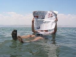 A tourist (on the Jordanian side) demonstrates the unusual buoyancy caused by high salinity.