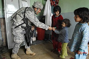 178th Infantry Regiment (United States) - SGT Heriberto Medina, 1-178, gives school supplies to a girl in a hospital in Paktia Province, Afghanistan. 17 February 2009.