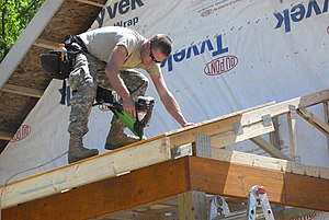 Framer - A framer in the United States nailing the roof decking to prefabricated trusses using a nail gun. His tool belt and safety glasses are typical. Hearing protection and fall arrest equipment is missing.