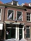 foto van Woonhuis van parterre en verdieping met lijstgevel, waarin oorspronkelijke deur met bovenlicht en kalf. Links inrijdeur. In de verdieping zesruitsschuiframen