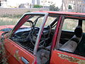 Destroyed red car in a abandoned zone nearnear amin eslami garden- Nishapur 1.JPG