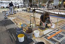 Dans un immense atelier, quelqu'un dessine avec soin une colonne au milieu des pots de peinture.