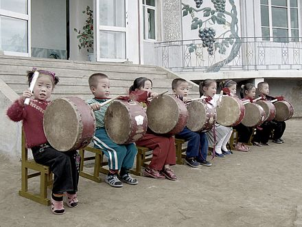 North Korean children performing for tourists at Chonsam Cooperative Farm near Wonsan Drumming children.jpg
