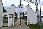 Cemetery gate with bars and tombstone