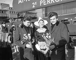 Two young men wearing long coats, holding bunches of flowers, standing either side of a woman in traditional Dutch clothing
