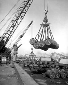 Several barrels being lifted off a ship by a crane