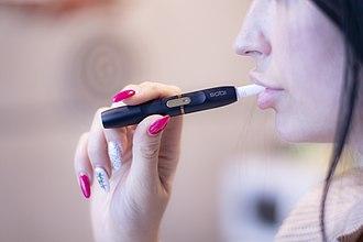 Philip Morris International - Girl smoking tobacco device IQOS.