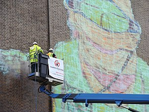 OSGEMEOS - The 2008 Tate Modern exhibition Street Art ends, appropriately, with graffiti removal on a large scale. Here, a massive figure by OSGEMEOS, one of six artworks on the riverside façade, is removed by specialists using steam jets operating from a cherry picker.