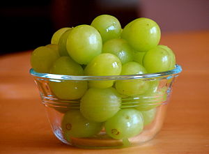 Some green grapes in a small, clear bowl.