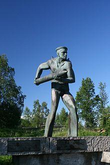 Brązowy pomnik, przedstawiający postać marynarza w lekkim wykroku w trakcie działoczynów (podającego amunicję do działa). Pomnik stoi na betonowym, niskim cokole, z dwoma tablicami. W tle niskie drzewa na trawiastym, niskim wzgórzu.