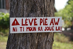 Antillean Creole - Road sign in residential area in Guadeloupe. Slow down. Children are playing here.