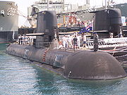 A submarine next to a dock, with navy personnel and civilians standing on the outer hull. Parts of another submarine and two warships can be seen in the background.