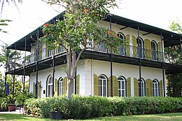 two story square house with tall windows and exterior shutters and a second story porch