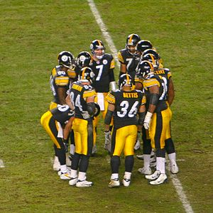 Huddle - Pittsburgh Steelers in an NFL huddle.  Offensive players gather in a rough circle out of hearing of the opposing defense to plan the next play.