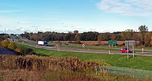 "A divided highway going across a level landscape. On the right is a sign in English and French saying ""Last U.S. Exit/Derniere Sortie EE. U."" On the left the road goes away from the camera, up a slight rise to a more built-up area with a tall antenna."