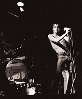 A rock band is onstage. A drumkit is on the left. A singer, Iggy Pop, sings into a microphone. He is wearing jeans and has no shirt on.