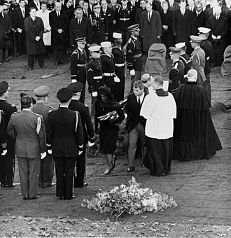 John F. Kennedy Eternal Flame - Mrs. Kennedy and AG Robert F. Kennedy walk away from President Kennedy's casket after lighting the Eternal Flame. The evergreen boughs which cover the base of the temporary Eternal Flame can be seen behind them. The Presidential Honor Guard is in front of and to the left of Mrs. Kennedy. Note the presence of the Green Beret.