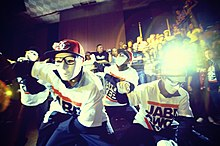 A close-up shot of a performance by four young men in a hip-hop dance crew dressed in black slacks, white t-shirts, white face masks, and red baseball caps.