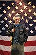 A color photo of an older white man in a leather jacket with a large American flag in the background. He is looking down toward the ground and is holding a microphone.