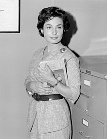 A woman holds a clipboard while standing next to a filing cabinet.