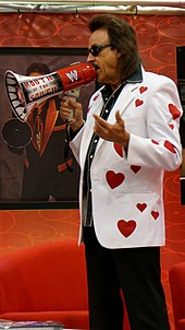 Jimmy Hart, holding a megaphone and wearing a white jacket with red stars on it