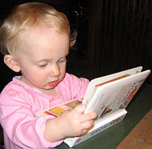 Un bébé est assis sur le sol. Il regarde un livre qu'il tient entre ses mains avec une expression d'intérêt et de concentration.