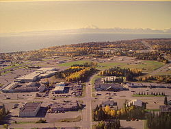 Aerial view of part of downtown Kenai.  The intersection of Willow Street and Barnacle Way is in the center of the foreground.  Cook Inlet and Mount Redoubt are in the background.