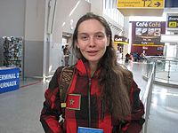 A woman with long brown hair faces the camera, she wears a red and black checked jacket.