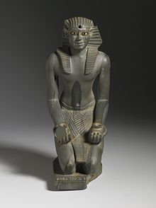 Grey statue of kneeling pharaoh, with vases in its hands