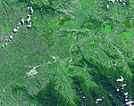 Satellite image of a green valley dominated by farming and agriculture
