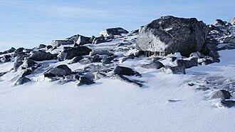 Kulusuk - Moraine boulders under Qalorujoorneq: rime ice windblasted on the northeast-facing surfaces