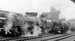 Royal Scot (train) - Princess Coronation class locos changing over at Carlisle on the southbound Royal Scot in 1958. 46221 Queen Elizabeth (left) with 46240 City of Coventry with headboard ready to go south