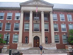 "A photograph of the entrance to a building displaying three stories of windows, a four-column portico, and a sign reading ""BOSTON LATIN SCHOOL""."