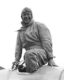 Informal half portrait of man in flying suit with cap and googles emerging from the open cockpit of an aeroplane