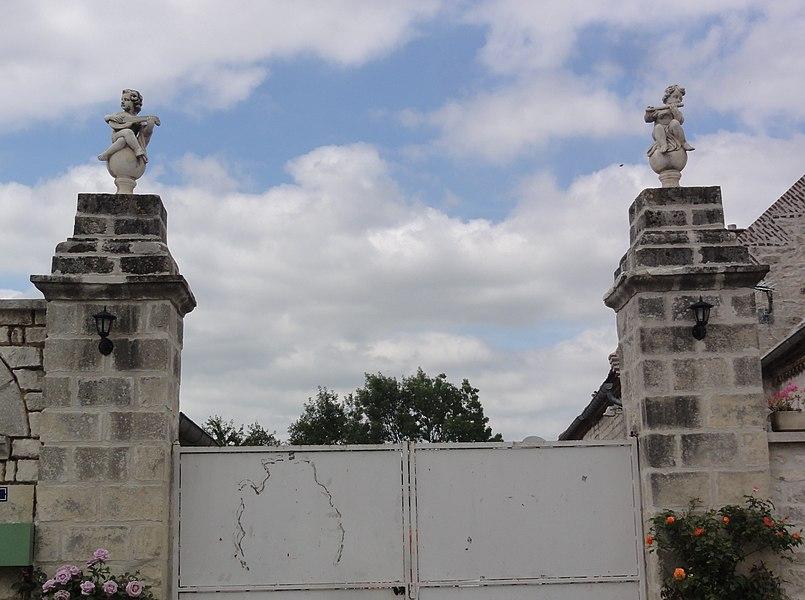 Mâchecourt (Aisne) statuettes sur porte de ferme
