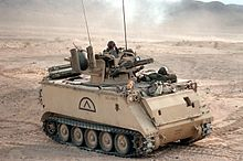 An armored vehicle containing several soldiers in a desert