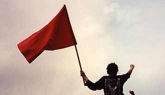 Marxism - Leftist protester wielding a red flag with a raised fist, both are symbols of revolutionary socialism.