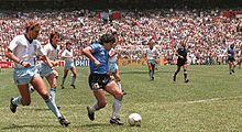 Photographie en couleurs. Le joueur argentin est en possession du ballon au centre de la photo, avec le joueur anglais le poursuivant, à gauche.