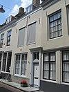 foto van Huis met gepleisterde rechte gevel. Voordeuromlijsting in eenvoudige Lodewijk XVI trant. Stoep