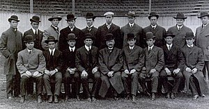 Black and white formal portrait of 10 young men standing and 9 seated in front of them. Most wearing formal hats, overcoats and suits.
