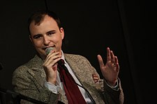 Photo of Jesse Thorn speaking into a microphone. He is caucasian and wearing a coat and tie.