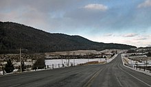 A two-lane paved road curves rightward away from the viewer toward a rise in the center of the image amid a snowy landscape of fields and woodlots under mostly cloudy skies, with a ridge of hills on the left