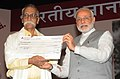 Narendra Modi presenting the cheque of Prize Money of the 50th Jnanpeeth Award to Prof. Bhalchandra Nemade, at the 50th Jnanpeeth Award Ceremony, at Balayogi Auditorium, Parliament Library, in New Delhi on April 25, 2015.jpg